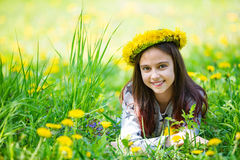 Cute young girl wearing wreath of dandelions and smiling. While lying on grass in park Stock Photos