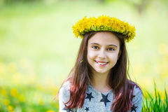 Cute young girl wearing wreath of dandelions and smiling. Outdoors Stock Photos