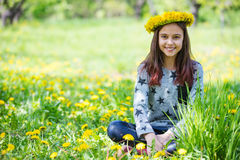 Cute young girl wearing wreath of dandelions and smiling. While sitting on grass in park Stock Image