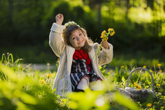 Cute young girl wearing wreath of dandelions and smiling while sitting on grass in park. Cute young girl weaving a wreath of dandelions and smiling sitting on Royalty Free Stock Photo