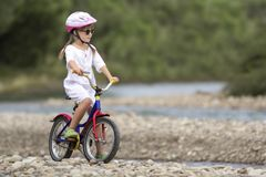 Cute young girl in white clothing, sunglasses with long braids wearing pink safety helmet riding child bicycle on pebbled river stock photos