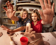 Cute young girls in a clay studio holding up their Stock Photo