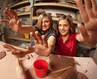 Cute young girls in a clay studio holding up their Stock Photos