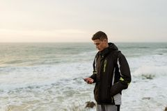 The guy is clapping a phone against the sea. Cute young guy clapping phone on sea background with waves Royalty Free Stock Image