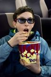 Cute young guy in a jacket eats popcorn sitting in a cinema chair. A teenager in 3D glasses puts his hand to his mouth and royalty free stock image