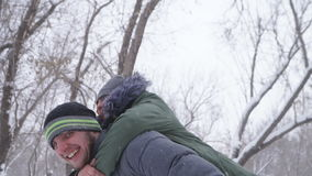Cute young guy piggybacking his girlfriend happy in the winter in the woods in the snow. Slow motion stock footage