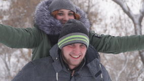 Cute young guy piggybacking his girlfriend happy in the winter in the woods in the snow. Slow motion stock video footage