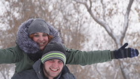 Cute young guy piggybacking his girlfriend happy in the winter in the woods in the snow. Slow motion stock video