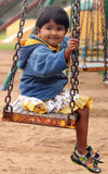 Cute young happy indian girl(kid) playing on a swing in a park Stock Image