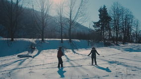 Cute young hipster couple having fun in winter park on a bright day hugging each other and smiling stock footage