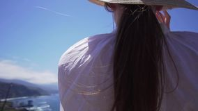 Cute young hipster woman posing for the camera, standing on the edge of a cliff above the Atlantic Ocean. Model on the. Island of Tenerife, Spain fullhd stock video