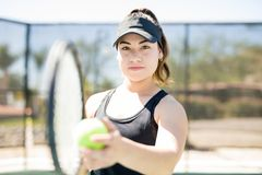 Female athlete playing tennis on court. Cute young hispanic female athlete in her 20s holding racket and ball for serving on tennis court Stock Photography