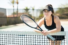Tennis player taking a break after training. Cute young hispanic female tennis player holding a racket leaning on the net looking away and smiling Stock Images