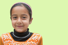 Cute young Indian girl with smiling pose  on soft green backdrop, ample empty space for text. Pretty young Indian girl with smiling pose  on soft green backdrop Royalty Free Stock Images