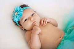 Cute young infant girl in a blue tutu and flower head band on  white blanket Royalty Free Stock Photo