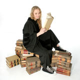 Cute Young Judge. Young woman sitting on 70 year old law books covered in dust.  Wearing judge's robe and black sneakers Royalty Free Stock Images