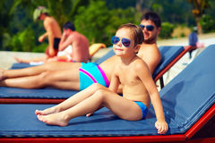 Cute young kid, boy relaxing on lounge during summer vacation Royalty Free Stock Photo