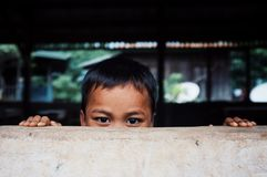 cute young kid hiding behind a wall peaking his head just above stock photography