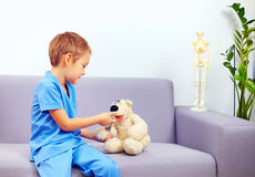 Cute young kid playing a doctor in office Stock Image