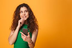 Cute young lady chatting by mobile phone. Image of cute young lady standing over yellow background. Looking aside chatting by mobile phone stock photos
