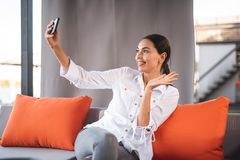 Cute young lady waiving her hand while having video call royalty free stock photography