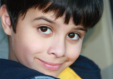 Cute Young Latino with Big Eyes. Adorable and happy boy smiling with big eyes and chin tucked behind his sweatshirt royalty free stock photo