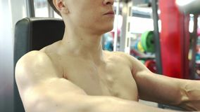 Cute Young Male Bodybuilder Engaged With An Exercise Machine To Train Shoulders Muscles. Close-up - Cute Young Male Bodybuilder Engaged With An Exercise Machine stock footage