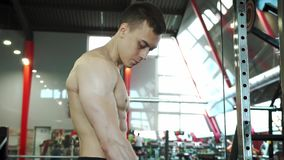 Cute Young Male Bodybuilder Training Biceps in Exercise Machine. Cute Young Male Bodybuilder Engaged With An Exercise Machine To Train Biceps Muscles. Healthy stock video footage
