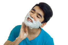 Cute young man in blue t-shirt with shaving cream on his face smiling Royalty Free Stock Images