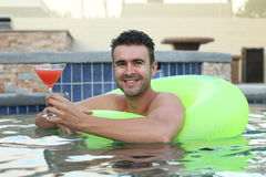 Cute young man drinking a cocktail while relaxing in a swimming pool.  Royalty Free Stock Photo