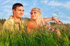 Cute young man and fine woman sit on meadow. Stock Photography