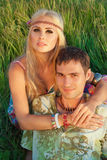 Cute young man and fine woman sit on meadow. Stock Image