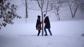 Cute young man and girl spend their leisure time in a snow-covered park. Date of young couple. Happy couple in love stock video