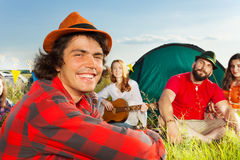 Cute young man in hat sitting with friends at camp Stock Photo