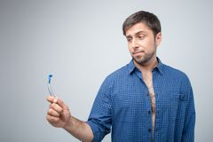 Cute young man is thinking about shaving his beard Royalty Free Stock Image