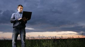 Cute young man working on laptop at sunset on the field. Beautiful sky on a background. stock video