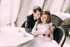 Cute young married couple hugging sitting in coffee shop Royalty Free Stock Image