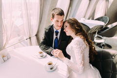 Cute young married couple hugging sitting in coffee shop Royalty Free Stock Photography