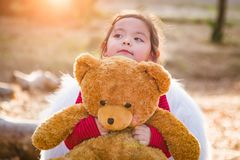 Little Mixed Race Baby Girl Hugging Teddy Bear Outdoors. Cute Young Mixed Race Baby Girl Hugging Teddy Bear Outdoors royalty free stock photography