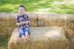 Cute Young Mixed Race Boy Having Fun on Hay Bale Royalty Free Stock Photos