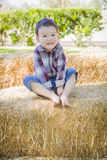 Cute Young Mixed Race Boy Having Fun on Hay Bale Stock Image