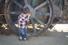 Cute Young Mixed Race Boy Having Fun Near Antique Machinery Royalty Free Stock Photo