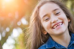 Laughing Mixed Race Girl Playing in the Sunshine Outdoors. Cute Young Mixed Race Girl Having Fun in the Sun Outdoors royalty free stock image