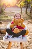 Cute Young Mixed Race Girl Hugging Teddy Bear Outdoors. Cute Young Mixed Race Girl Hugging a Teddy Bear Outdoors royalty free stock photos