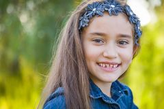 Precious Mixed Race Girl Playing in the Trees Outdoors. Cute Young Mixed Race Girl Having Fun in the Sun Outdoors stock photos