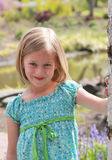 Cute Young Model. Playful 5 year old smiles and models a blue and green dress Stock Photos