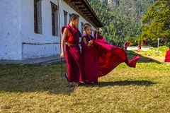 Cute Young novice monk let his robe fluttering in the wind , eastern Bhutan royalty free stock photography