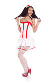 Cute young nurse looking aside. Full body shot of a happy sexy beautiful young nurse wearing red high heels shoes looking aside on isolated white background Stock Photography