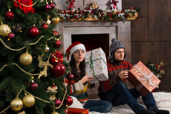 Cute young pair guessing at their Christmas gifts holding a boxe Stock Photo