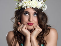 Cute young pensive beauty model wearing floral wreath with head in hands looking up Stock Image
